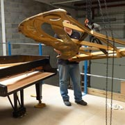 The cast steel plate of a Steinway grand piano is removed.